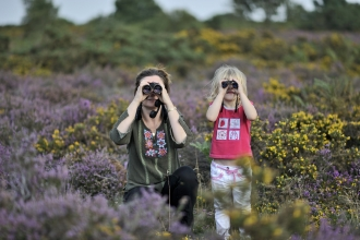 Happy family birdwatching among heather