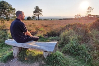 Man sits on bench overlooking heathland