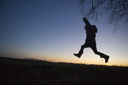 Child leaping against sky-line