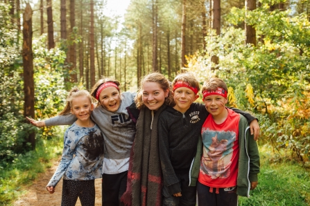 Five children, faces painted, in woodland