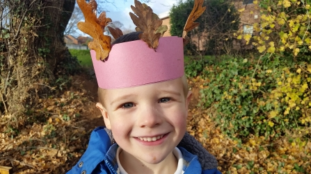 Child with a leaf crown at forest school