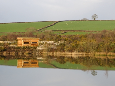 Bird hide reflection at Meeth Quarry