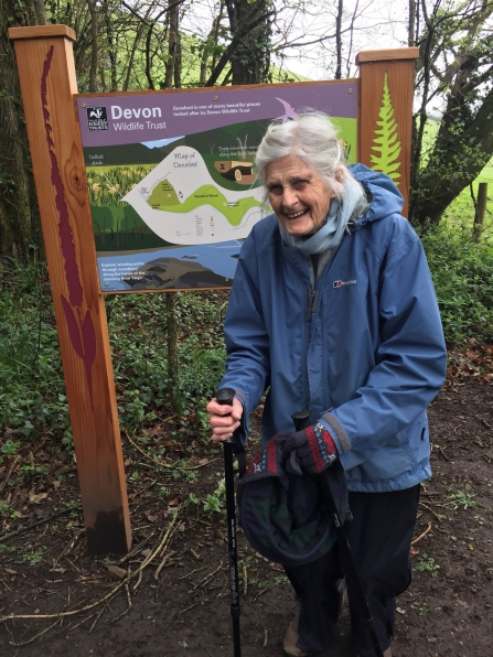 Woman stands in front of nature reserve sign