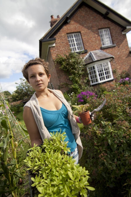 Gardening with wildlife, woman walking along with pack of plug plants, house and garden in background