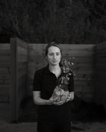 Portrait of woman holding sapling. Black and white.
